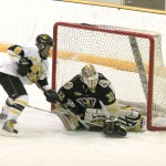 Whitney Schaff attempts to tip the puck past St. Olaf goaltender Jessica Ptachik.