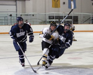 Whitney Schaff battles two Bethel players for control of the puck at center ice.