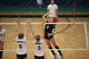 Outside hitter Janey Helland attacks the Cardinal block.