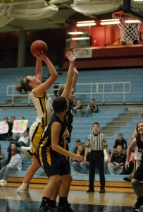 Julia Schultz goes up over two Carleton players for two of her 16 points.