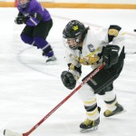 Melissa Mackley pushes the puck up the ice.
