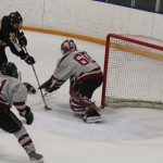 Rory Dynan slides the puck through the legs of Beau Christian of Hamline for the gamewinner for the Gusties. (Photo by Ryan Coleman)