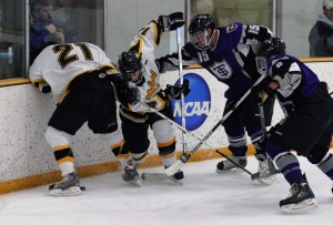 Joe Welch (21) and T.J. Ridley (14) battle the Tommies' Alex Arnason (25) along the boards.