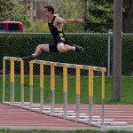Colin Rust leaps over a hurdle at the Gustie Invitational
