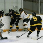 Kelly Thotland fights for a loose puck on the boards against UW-Superior's