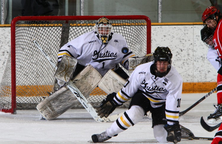 Senior Ross Ring-Jarvi attempts to block a shot while rookie goaltender John McLean waits to react behind him.  Photo courtesy of A.J. Dahm of Sport PiX.