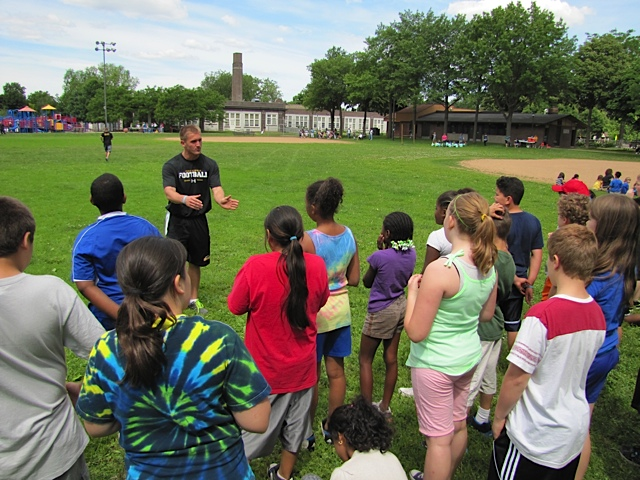 Cornerback Zach Dilger instructs campers at the Hiawatha Community School's annual Field Day.