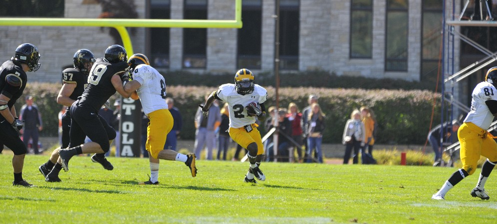 Slot receiver Phillip Butler bursts through a hole last season against St. Olaf.  The Gusties will look to avenge last year's 44-26 loss to the Oles on Manitou Field this Saturday. Photo courtesy of Mike Ludwig, St. Olaf Sports Information Director.
