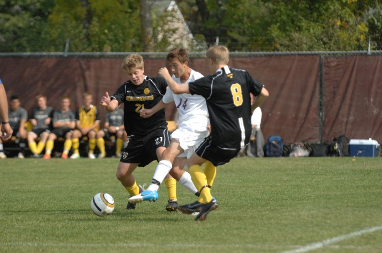 Gustavus' Charlie Adams and David Lilly converge on Concordia's Michael Forston Saturday afternoon in Moorhead.  Photo courtesy of Jim Cella - Concordia Sports Information Director