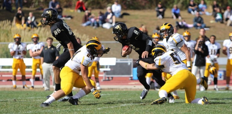Joe Haas wraps up St. Olaf quarterback Dan Dobson. Photo courtesy of Abigail Davis and Kyle Obermann - St. Olaf College