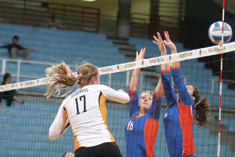 Emily Phillips hammers the ball through the block of two Macalester players. Photo take by Dan Coquyt - Gustavus Sports Information.