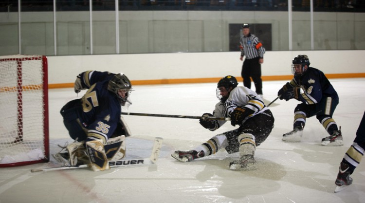 Adam Smyth gets tripped up as he challenges the Bethel goaltender in Saturday night's 2-0 loss.  Photo courtesy of Dan Coquyt - Gustavus Sports Informaiton