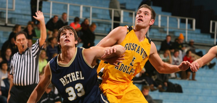 Bethel's Kyle Zimmerman (33) and Gustavus' Jim Hill (5) battle for a rebound in their first meeting this season. (Photo courtesy of A.J. Dahm - Sport Pix)