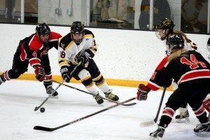 Carolyn Draayer battles a pair of Falcon defenders.