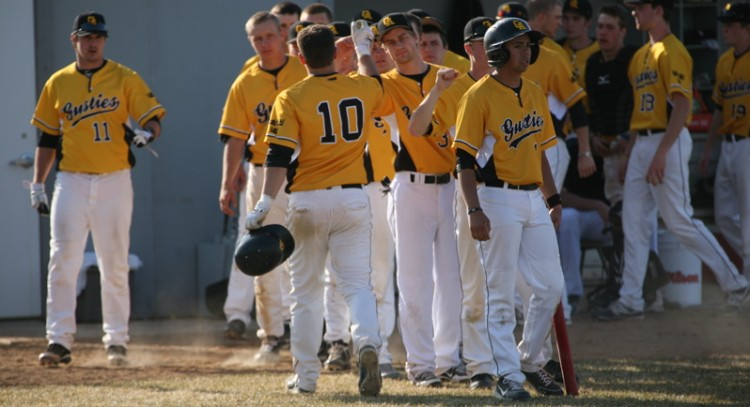 Drew Block (10) is greeted by his teammates after scoring a run.