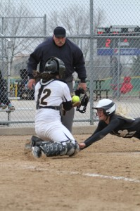 Kat Dahl puts the tag on a sliding Alex Lebens at home plate.