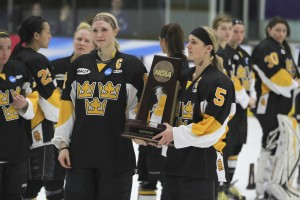 Branded with temporary neck tattoos that became a staple on the women's hockey team at the NCAA Semifinals over the past four years, Hjelm and fellow captain Jenna Christensen accept the fourth place trophy to cap their collegiate careers.