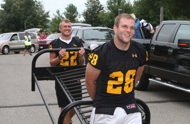 Seniors Lucas Kleinschrodt (#28) and Mitch Moore (#22)  team up to carry in a futon on first-year move-in day.