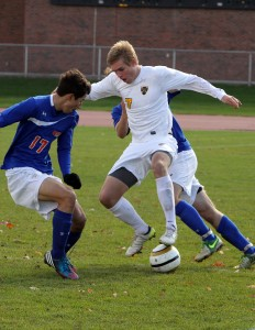 Ryan Tollefsrud fights to maintain possession against a pair of Scot defenders. Photo courtesy of Laura Westphal - Sport PiX.