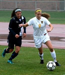 Amanda Cartony holds off a Bethel defender.