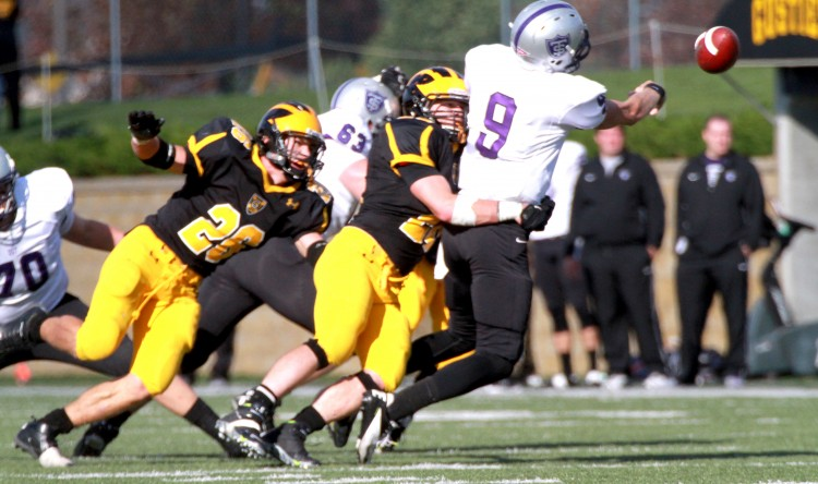 Senior linebacker Lucas Kleinschrodt pressures St. Thomas quarterback Alex Fenske. (Photo courtesy of Dan Coquyt '14)
