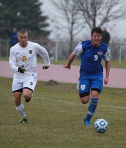 Gustavus's Elliot Emerson chases down St. Scholastica's top scorer Andrew Jenkins.