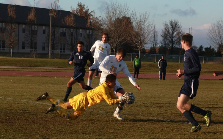Westminster goalkeeper Raul Romero dives and holds on to the ball as Gustavus's Patrick Roth bears down on him late in the second half.