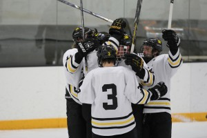 Teammates celebrate with Cory Ellis after his goal in the second period extended Gustavus's margin to two.