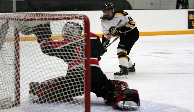An Allison Eder-Zdechlik shot is saved by the glove of UW-River Falls goaltender Ashley Kuechle.  (Photo courtesy of Dan Coquyt '14).