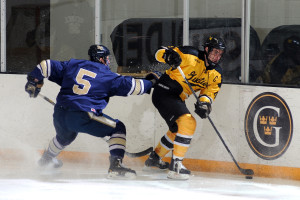 Jack Walsh works the puck off the boards against Bethel's Mitch Killian.  Photo courtesy of Sport PiX.