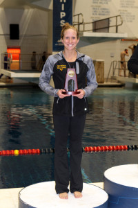 Alissa Tinklenberg on the podium with her eighth place trophy from Friday night's 100 backstroke.