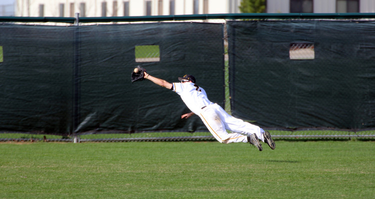 Senior Scott Benjamin makes a diving catch in center field on Monday afternoon against St. Olaf. Photo taken by Jessica Williams `16.