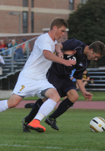 Ryan Tollefsrud battles Carleton's Trent Elmore.  Tollefsrud extended his point-streak to five matches with a goal today.