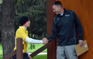 Captain shakes hands with MIAC Executive Director Dan McKane at the post-meet awards ceremony.