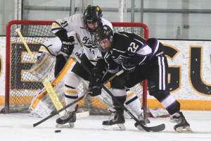 Jake Bushey ties up St. Thomas's Derek Jacobson in front of his goaltender.