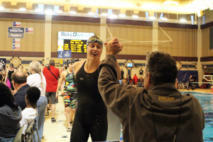 Jenny Strom gives Jon Carlson a high five after her swim in the 100 breaststroke.
