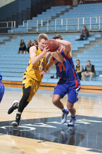 Brian Jacobs drive the lane against Macalester's Luke Poulsen. (photo by Chris Coquyt)